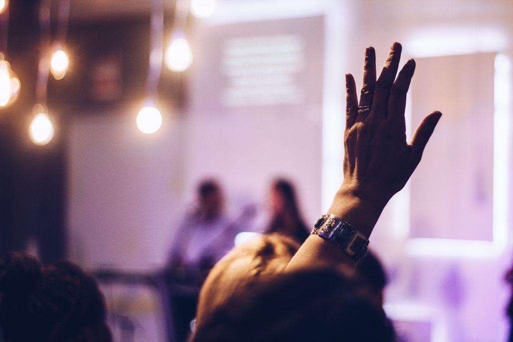 Ein Bild eines Vortrags, in dem im Vordergrund eine Damenhand zusehen ist, welche sich zu Wort melden möchte.