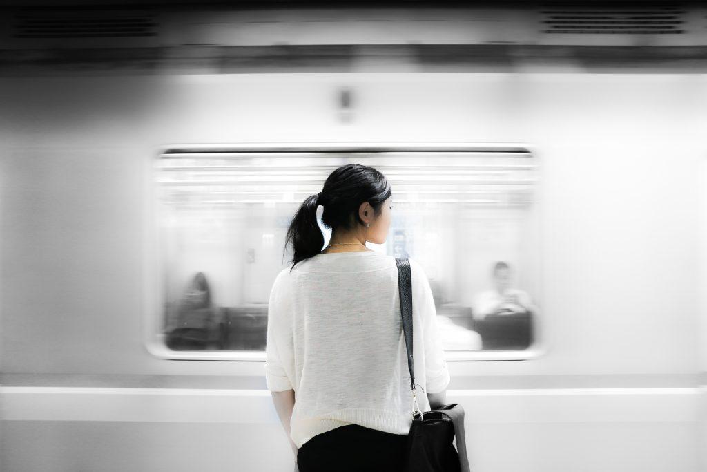 Fenster eines vorbeifahrenden Zuges, in dem eine Frau von hinten im Vordergrund zusehen ist.