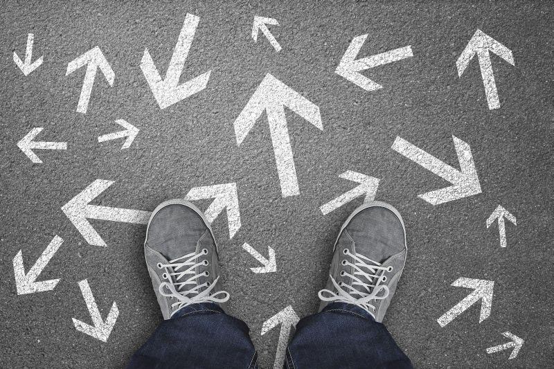 Füße einer Person, die Turnschuhe tragen, auf einem Boden dem mit lauter Richtungspfeile, die in verschiedene Richtungen zeigen.