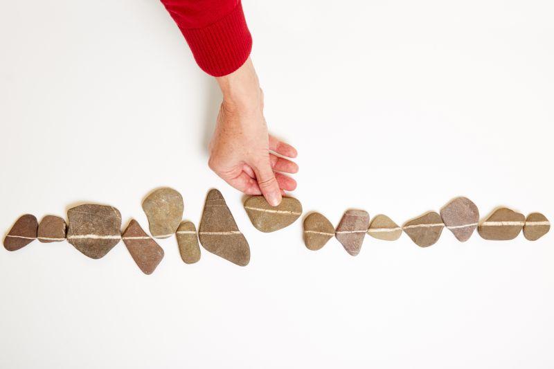 Eine Reihe mit Steinen, die eine Linie bilden und ein Hand einen Stein in die Mitte der Linie legt