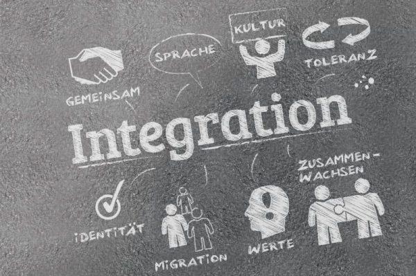 Graues Bild mit der Aufschrift Integration, davon gehen Symbole mit Begriffen weg, die Begriffe sind: Gemeinsam, Sprache, Kultur, Toleranz, Identität, Migration, Werte und Zusammenwachsen