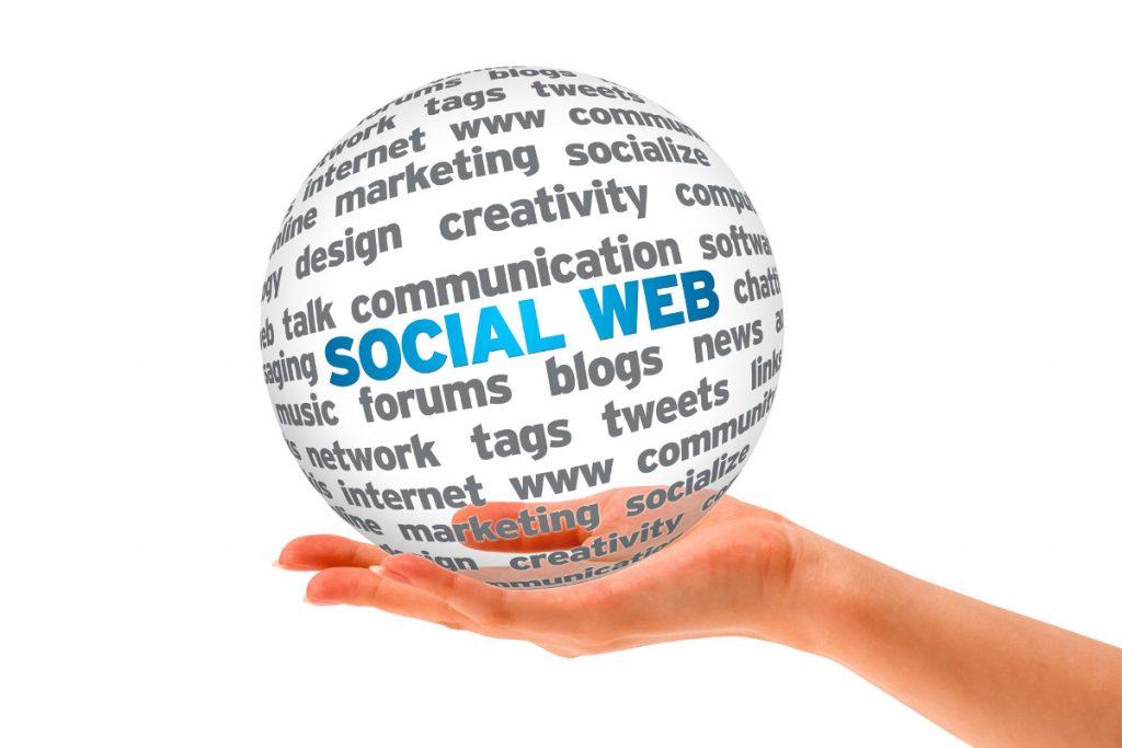 Eine Hand, die eine Kugel hält, in der verschiedene Begriffe stehen, wie zum Beispiel; Social Web, Communication, Creativity, Marketing, Tags, Tweets, usw.